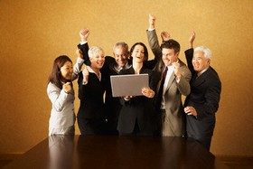 Group of businesspeople looking at laptop and cheering